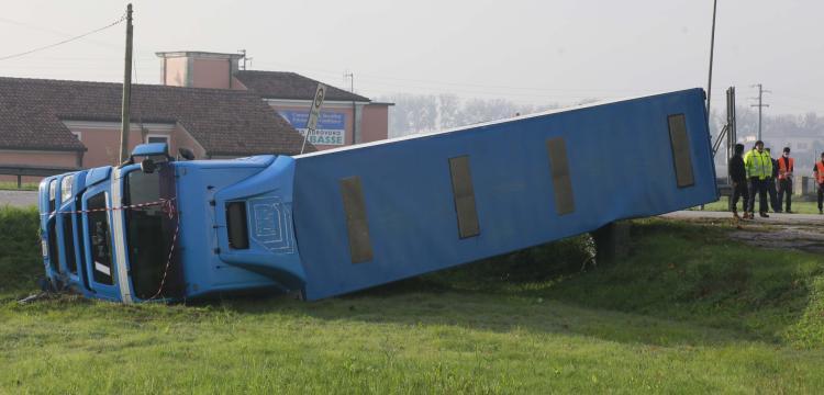 Perde il controllo ed esce fuori strada: camion si ribalta in rotatoria